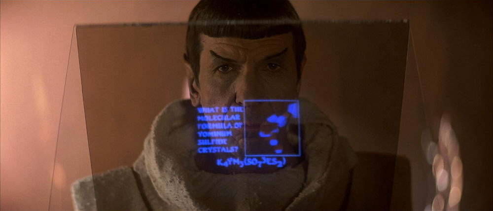 Spock standing in front of a transparent screen, looking at a possibly fictitious chemical compound.