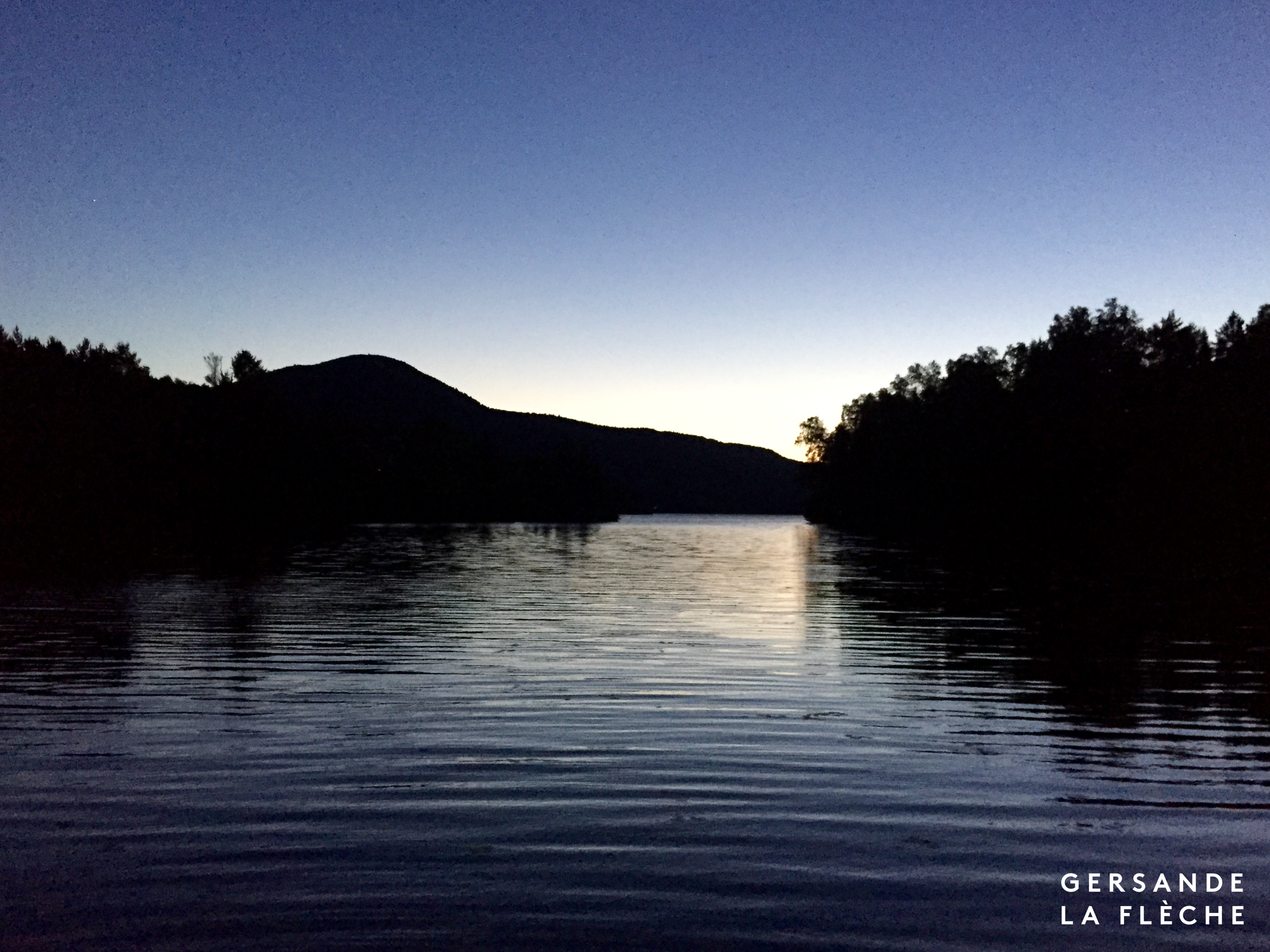 A photo of a mountain and a lake after sunset, with the silhouette of the forest reflected on the still silver-bright surface of the water.
