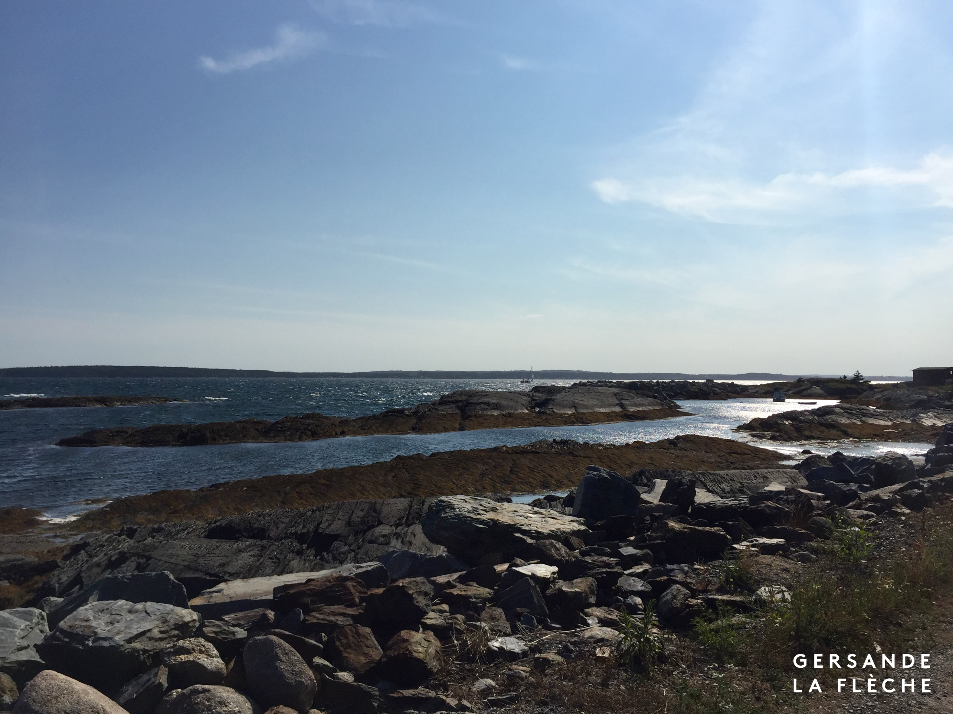 A picture of a blue sky over blue rocks lowering into the ocean.