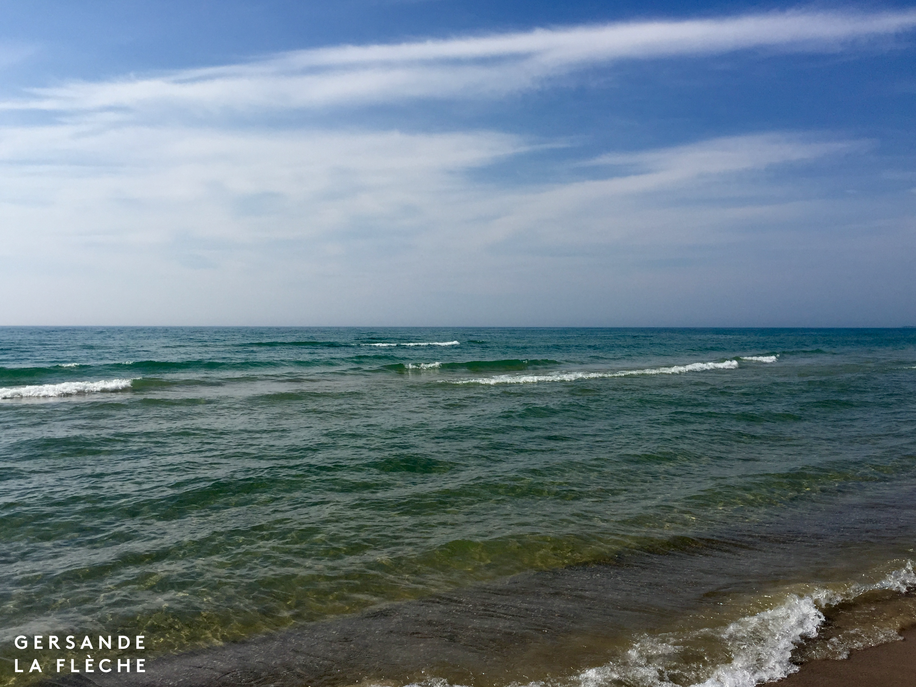 A picture of a blue sky, and the horizon of a immense lake, turquoise water that is also stunningly clear rolls into small waves as they reach the shore.