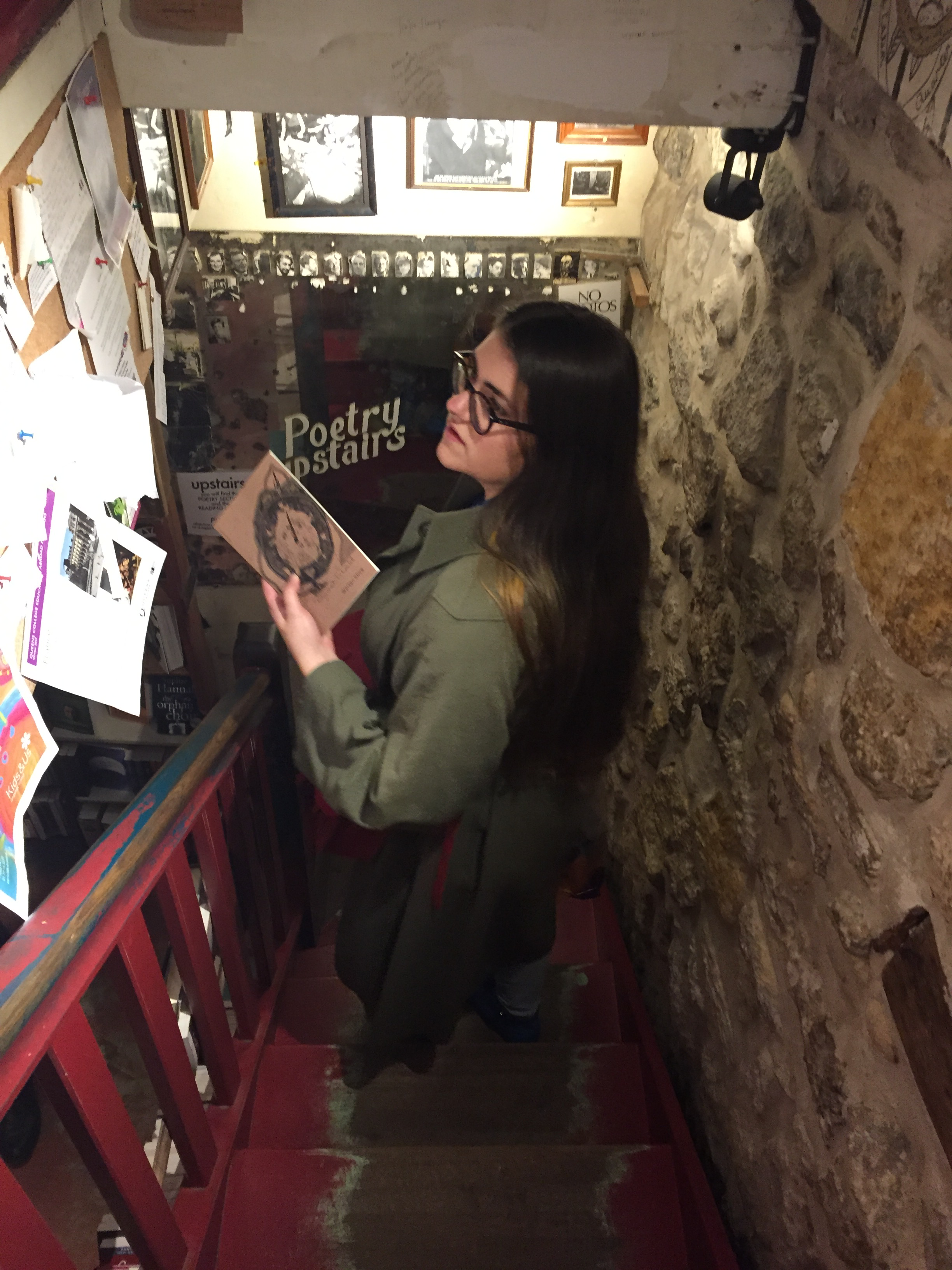 "A picture of me on a staircase in Shakespeare and Co, holding a copy of Warsan Shire's ""teaching my mother how to give birth"" and reading the bookstore's community board."