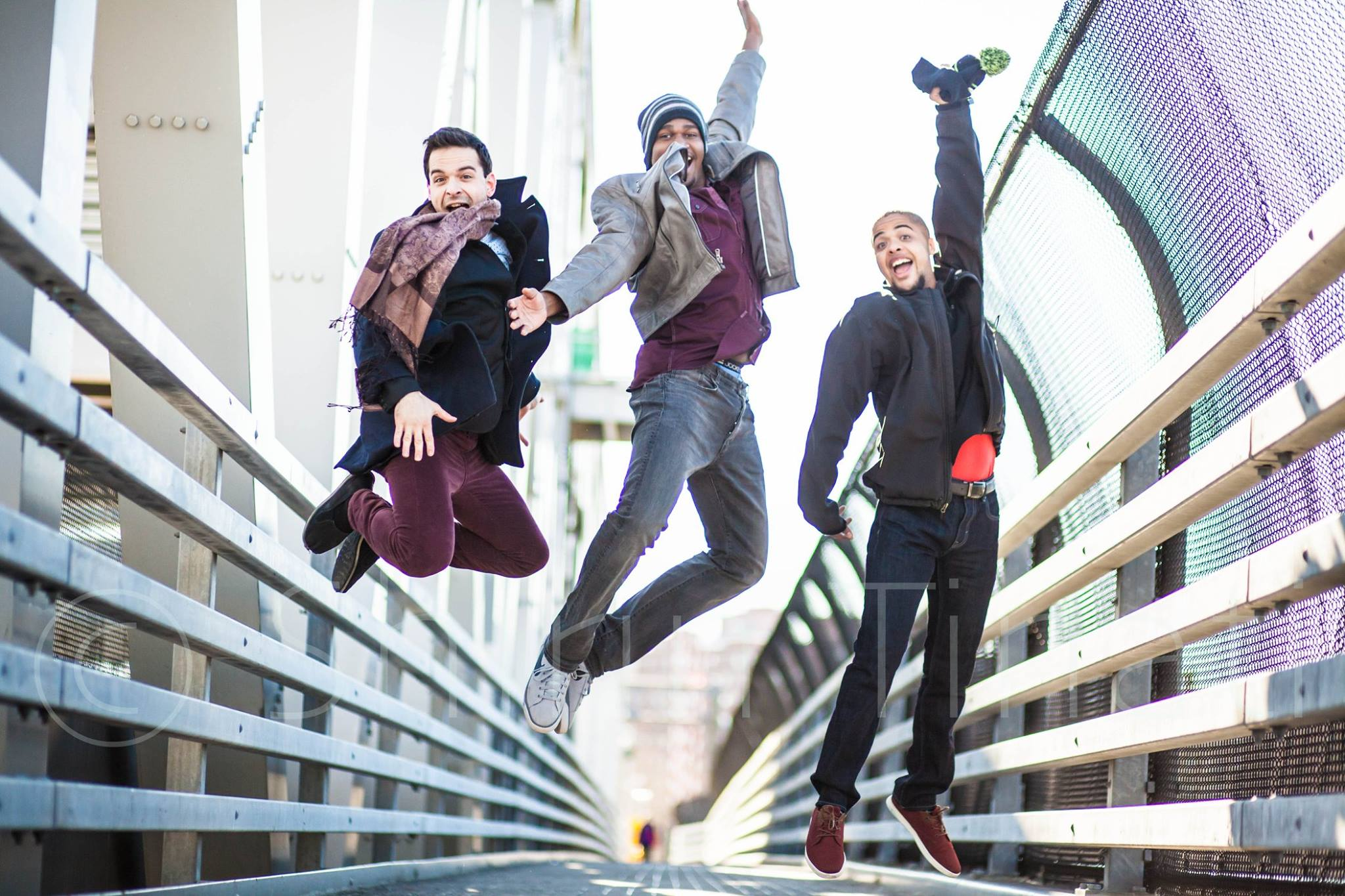 A photograph of Damien on a bridge with three friends, enjoying the day. Photo by Shirin Tinati.