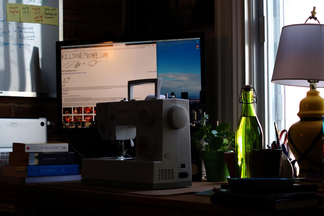 Une photo de mon bureau, avec la machine Singer Scholastic dessus. Il y a de nombreux livres et cahiers sur le bureau, incluant une bouteille d'eau et des petites plantes, et sur l'écran de l'ordi juste derrière la Singer on peut à peine distinguer les mots «KillYourPhone.com».