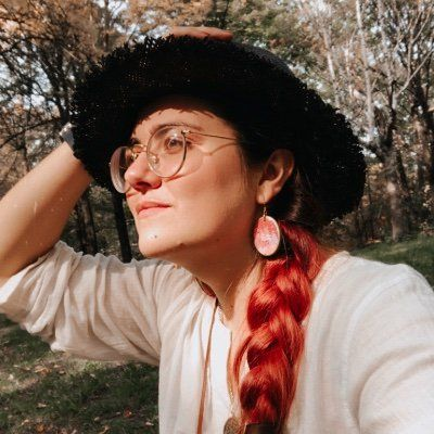 A photo of Gersande wearing a dark, wide-brimmed hat and a bright red braid hanging off their shoulder.
