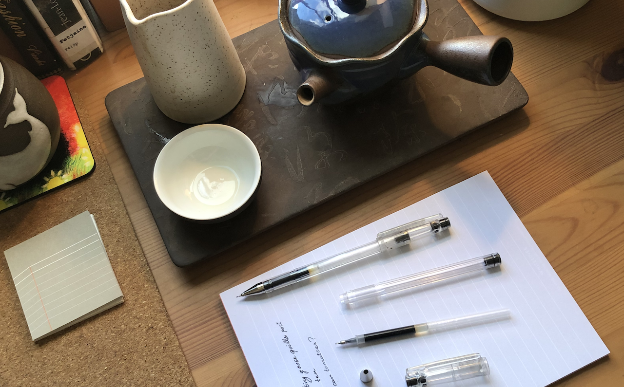 Une photo du haut de mon bureau, montrant des tasses de thé, une théière, des papiers, ainsi que deux stylos Pilot G-Tec, dont un qui a été démonté.
